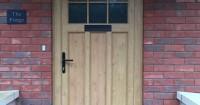 rectangular-light-brown-wooden-front-door-with-black-handle