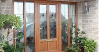 tan-wooden-front-door-with-large-panels-either-side