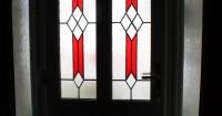 dark-brown-front-door-with-red-patterned-window-panel