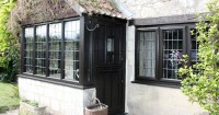 black-wood-effect-upvc-windows-with-thatched-roof