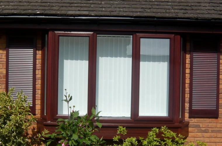 dark-brown-wood-effect-upvc-windows-with-green-bush